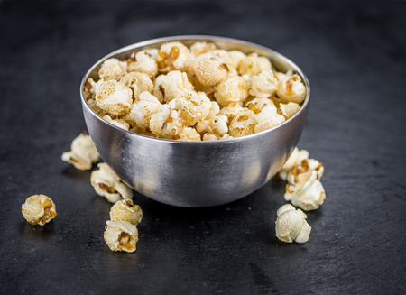 Fresh made Popcorn on a vintage background as detailed close-up shot Stock Photo