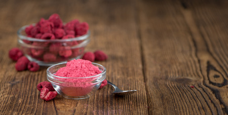 Raspberry powder as high detailed close-up shot on a vintage wooden table; selective focus