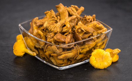 Portion of Preserved chanterelles on a rustic slate slab, selective focus, close-up shot