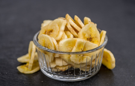 Some Dried Banana Chips on a slate slab as detailed close-up shot; selective focus
