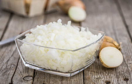 Chopped white onions on an old wooden table as detailed close-up shot; selective focus Banque d'images