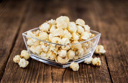 Popcorn as high detailed close-up shot on a vintage wooden table; selective focus