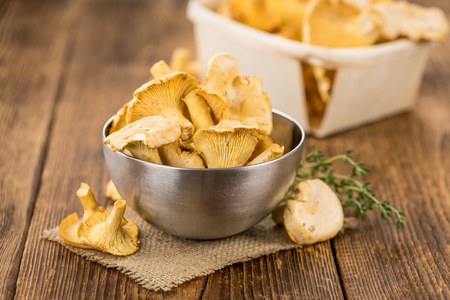 Portion of fresh harvested Chanterelles on wooden background as detailed close-up shot (selective focus)