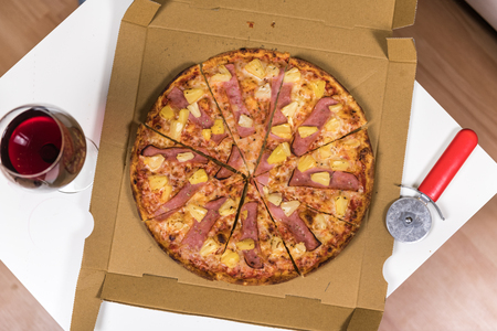 Fresh homemade Hawaiian Pizza on a modern table (view from above)