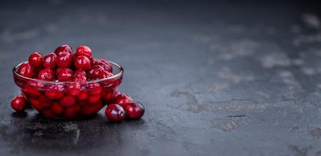 Healthy Canned Cranberries on a vintage slate slab (close-up shot; selective focus)