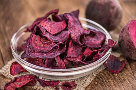 Some fresh Beetroot Chips on wooden background (selective focus; close-up shot) 免版税图像