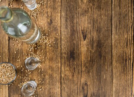 Vintage wooden table with Wheat Liqueur (selective focus; close-up shot)