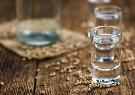 Wooden table with Wheat Liqueur (detailed close-up shot; selective focus) Standard-Bild