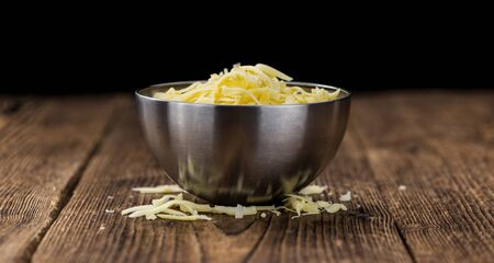 Old wooden table with grated Cheese (close-up shot) Standard-Bild