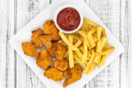 Vintage wooden table with fresh made Chicken Nuggets (close-up shot; selective focus)