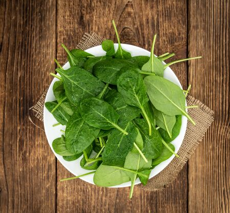 Vintage looking wooden table with fresh Spinach as detailed selective focus (close-up shot) Stockfoto