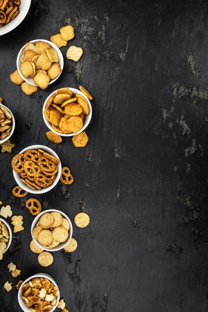 Portion of mixed Snacks on dark background (detailed close up shot; selective focus)