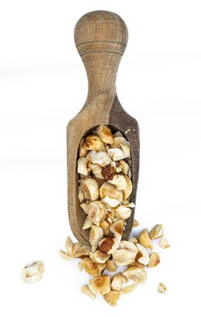 Freshly chopped Hazelnuts as detailed close up shot isolated on white background (selective focus)