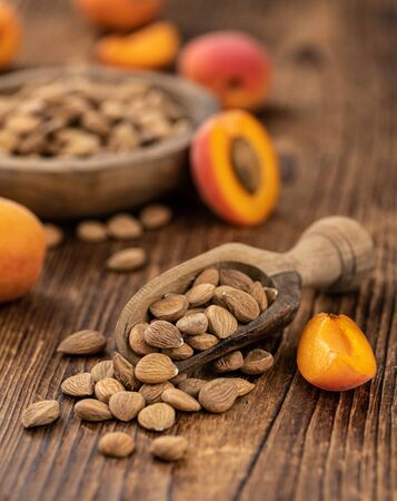 Vintage wooden table with a portion of shelled Apricot Kernels (close up shot; selective focus) 版權商用圖片