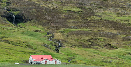 Lonely Farm in iceland with great landscape an waterfall in background