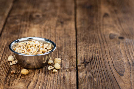 Portion of freshly chopped Hazelnuts on an old wooden table as detailed close up shot (selective focus)
