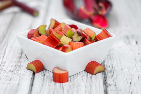 Chopped Rhubarb on an old wooden table (close up shot; selective focus) Reklamní fotografie