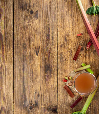 Rhubarb Juice on a rustic background (close up shot; selective focus)