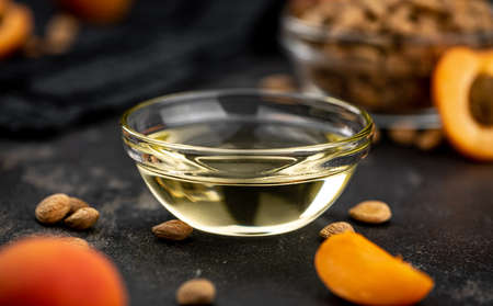 Portion of Apricot Oil with some fresh fruits as detailed close up shot (selective focus)