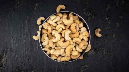Portion of roasted Cashew Nuts (close up shot; selective focus)