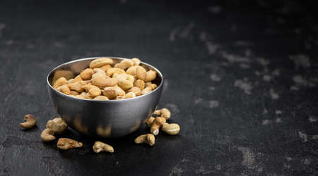 Some roasted Cashew Nuts as detailed close up shot (selective focus)