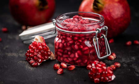 Some fresh preserved Pomegranate seeds (selective focus; close-up shot)