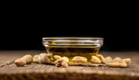 Fresh made Cashew Oil on an old wooden table (close-up shot; selective focus)