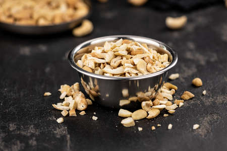 Slate slab with freshly chopped Cashew nuts (close-up shots, selective focus) Reklamní fotografie