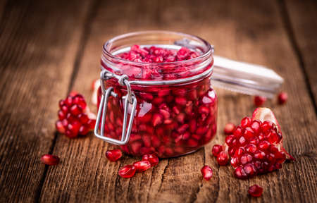 Vintage wooden table with preserved Pomegranate seeds (selective focus; close-up shot)