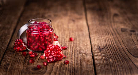 Portion of healthy preserved Pomegranate seeds on an old wooden table (selective focus; close-up shot)