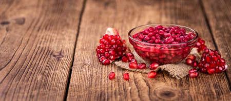 Some preserved Pomegranate seeds on a vintage wooden table (selective focus; close-up shot) Reklamní fotografie
