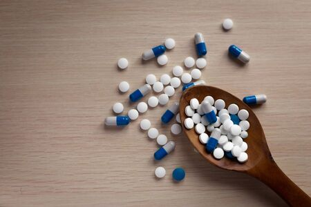 Assorted pharmaceutical white and blue medicine tablets, tablets and capsules on a wooden spoon