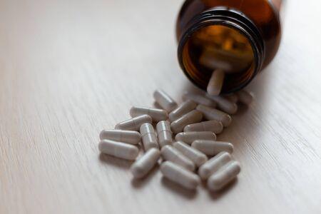 White medical pills and tablets spilling out of a drug bottle