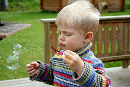 Small boy making soap bubbles outdoor at spring weather Stock Photo - 1106122