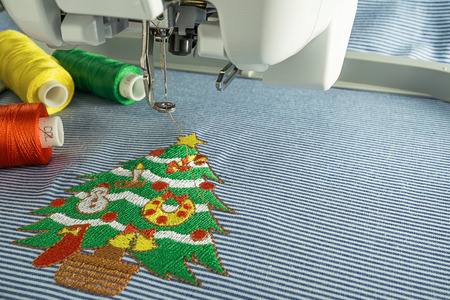 sewing machines: Background of close up image embroidery machine and embroidered  lovey christmas tree  have text space