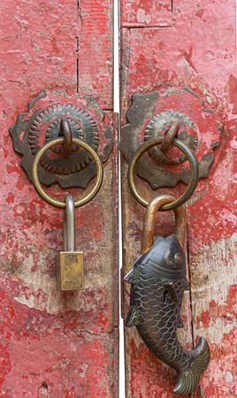 door handle: Close up of two padlocks regular shape and fish shape on the old red wood door
