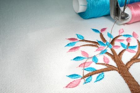 マシンのフープで白い綿生地に刺繍木漫画のスタイルを保持します。 クローズ アップ写真は、2 つのスレッドがシアン色やピンクのテクスチャを見