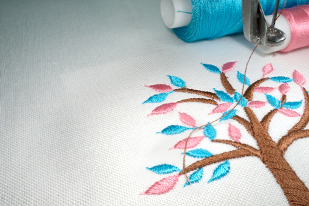 Embroidery tree cartoon style on white cotton fabric hold with the hoop in the machine