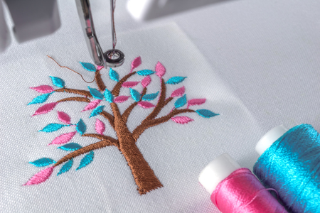 sewing machines: Marco close up image of embroidery cartoon tree design on workspace of machine and two threads cyan and pink color