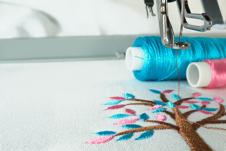 two: Picture of workspace in the embroidery machine close up look under the needle, lovely tree minimal sytle on background have two colorfull thread cyan and pink. Stock Photo