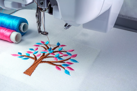 Close up picture workspace of  embroidery machine show embroider tree design theme. And two thraed s cyan and pnk color.