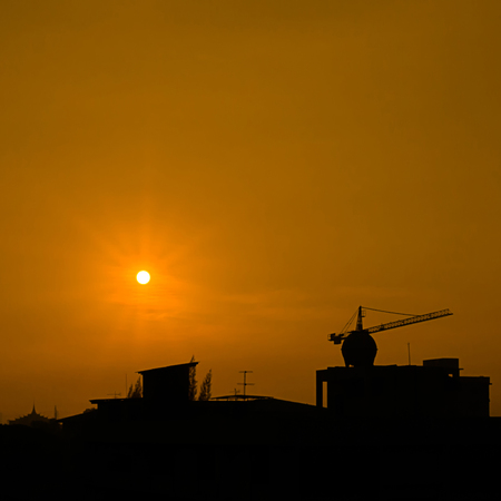 Sihouette background of sunrise on sky at hometown, shadow part is construction site, building and temple Stock Photo