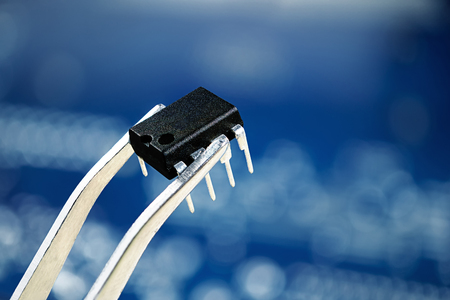Microchip bios on tweezer,close up photo, blur bokeh blue background Foto de archivo