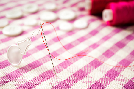 shiny buttons: Close up photo of sewing tools needle, red thread, threader, button on fabric Stock Photo