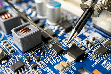 Repair microchip with soldering iron and tin, close up picture