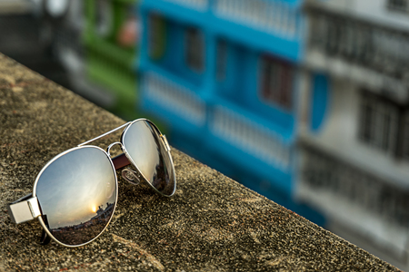 Sliver sunglasses have refraction of sunrise on the floor and blur background
