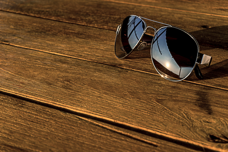 the sunglasses silver color is on the wood table and refraction of sunrise at morning, close up picture