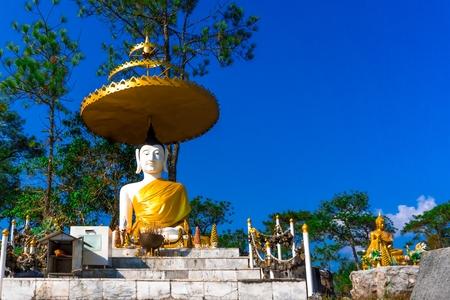 White buddha statue and small golden buddha sculpture at Phu Kradueng National Park, copy space, blue sky cloudless