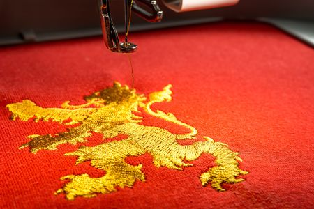 close up of embroidery machine and gold lion design on red fabric, copy space on the right side.