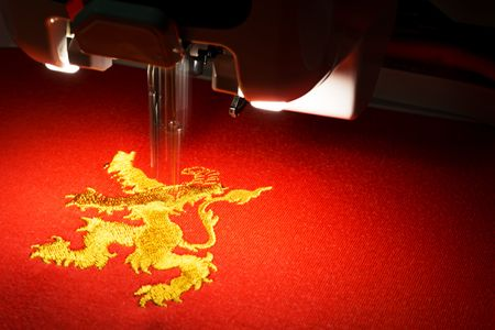The embroidery machine embrodering gold lion design on red fabric, close up picture, copy space on the right